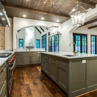 This is an example of a large industrial l-shaped separate kitchen in Dallas with an undermount sink, shaker cabinets, green cabinets, marble benchtops, red splashback, brick splashback, stainless steel appliances, dark hardwood floors, with island, brown floor and grey benchtop.