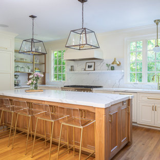 Design ideas for a large traditional u-shaped separate kitchen in Raleigh with an undermount sink, raised-panel cabinets, white cabinets, quartzite benchtops, white splashback, panelled appliances, medium hardwood floors, with island, brown floor and white benchtop.