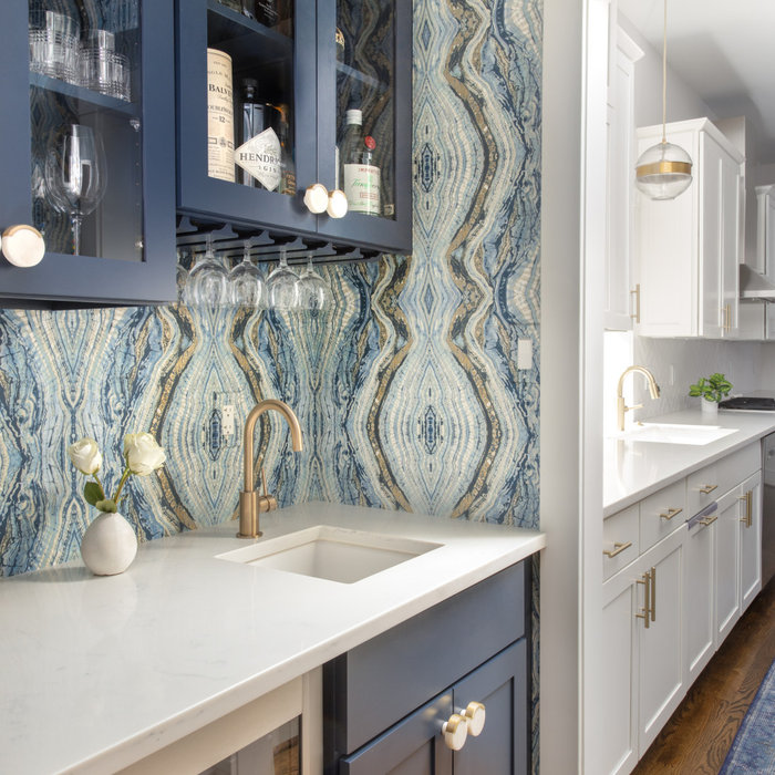 Who's ready for a cocktail? This Butler's Pantry was craving color! We gave it a luxe makeover with navy cabinetry, quartz countertops, and amazing dramatic wallpaper. The marble and brass cabinet kno