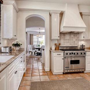Mittelgroße Klassische Küche ohne Insel mit Vorratsschrank, Einbauwaschbecken, weißen Schränken, Granit-Arbeitsplatte, Küchenrückwand in Beige, Rückwand aus Steinfliesen, Küchengeräten aus Edelstahl und Terrakottaboden in Santa Barbara