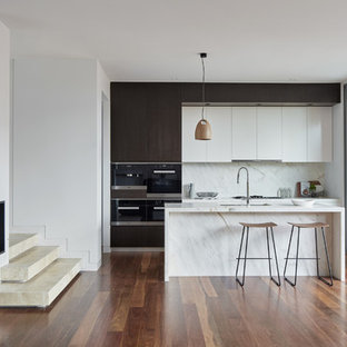 Photo of a mid-sized contemporary galley kitchen in Melbourne with an undermount sink, marble benchtops, white splashback, marble splashback, black appliances, medium hardwood floors, brown floor, white benchtop, flat-panel cabinets, dark wood cabinets and with island.
