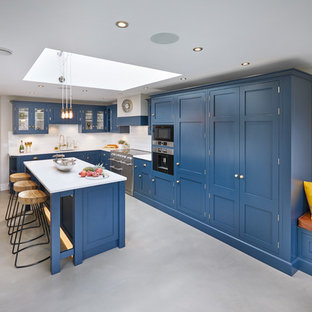 Photo of a large traditional l-shaped eat-in kitchen in Other with an integrated sink, shaker cabinets, blue cabinets, quartzite benchtops, white splashback, subway tile splashback, stainless steel appliances, concrete floors, with island, grey floor and white benchtop.