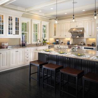 タンパの広いトランジショナルスタイルのおしゃれなキッチン (ドロップインシンク、レイズドパネル扉のキャビネット、白いキャビネット、御影石カウンター、茶色いキッチンパネル、御影石のキッチンパネル、シルバーの調理設備、濃色無垢フローリング、茶色い床、茶色いキッチンカウンター、格子天井) の写真
