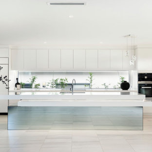 Expansive contemporary galley kitchen in Other with white cabinets, quartz benchtops, black appliances, with island and white benchtop.