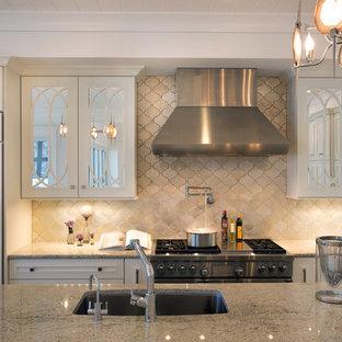 Mittelgroße Klassische Küche in L-Form mit Vorratsschrank, integriertem Waschbecken, weißen Schränken, Granit-Arbeitsplatte, Küchenrückwand in Beige, Rückwand aus Terrakottafliesen, weißen Elektrogeräten, Travertin und Kücheninsel in Miami