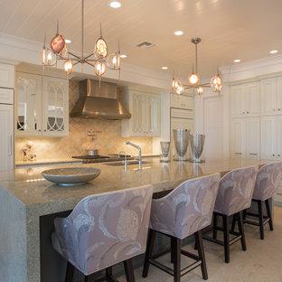 Bild på ett mellanstort vintage l-kök, med luckor med infälld panel, vita skåp, granitbänkskiva, beige stänkskydd, stänkskydd i terrakottakakel, integrerade vitvaror, travertin golv och en köksö