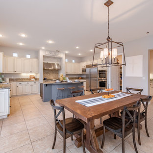 This is an example of an expansive mediterranean u-shaped open plan kitchen in Los Angeles with a drop-in sink, flat-panel cabinets, light wood cabinets, granite benchtops, beige splashback, porcelain floors, with island, beige floor and beige benchtop.
