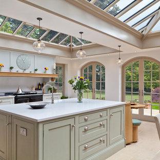 Große Klassische Wohnküche mit Kassettenfronten, grünen Schränken, schwarzen Elektrogeräten und Kücheninsel in Sonstige