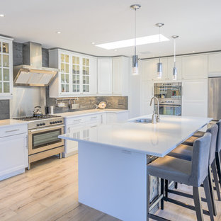 Expansive beach style galley open plan kitchen in Toronto with a double-bowl sink, beaded inset cabinets, white cabinets, laminate benchtops, grey splashback, stone tile splashback, stainless steel appliances, light hardwood floors and with island.
