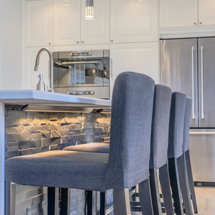 Photo of an expansive beach style galley open plan kitchen in Toronto with a double-bowl sink, beaded inset cabinets, white cabinets, laminate benchtops, grey splashback, stone tile splashback, stainless steel appliances, light hardwood floors and with island.