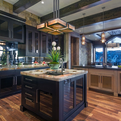 Example of a large trendy u-shaped medium tone wood floor enclosed kitchen design in Denver with black cabinets, glass-front cabinets, an undermount sink, metallic backsplash, mirror backsplash, stainless steel appliances and an island
