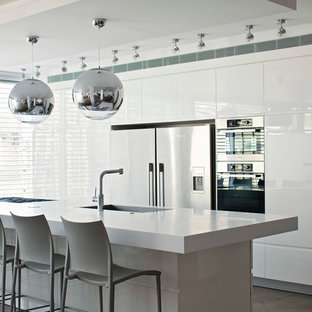 Mid-sized contemporary galley eat-in kitchen in Tel Aviv with an integrated sink, flat-panel cabinets, white cabinets, quartzite benchtops, stainless steel appliances and slate floors.