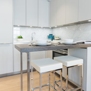 Design ideas for a small contemporary l-shaped kitchen in London with a submerged sink, flat-panel cabinets, grey cabinets, composite countertops, marble splashback, light hardwood flooring, white worktops, white splashback, a breakfast bar and beige floors.