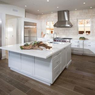 Esempio di una cucina stile marino di medie dimensioni con lavello sottopiano, ante in stile shaker, ante bianche, top in marmo, paraspruzzi beige, paraspruzzi con piastrelle in pietra, elettrodomestici in acciaio inossidabile, parquet scuro, isola e pavimento marrone