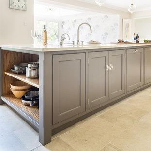 Modelo de cocina lineal, clásica renovada, de tamaño medio, abierta, con fregadero de doble seno, armarios con paneles empotrados, suelo de piedra caliza y una isla