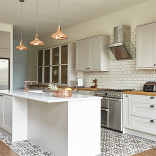 Classic galley kitchen in London with a belfast sink, shaker cabinets, white cabinets, wood worktops, white splashback, metro tiled splashback, stainless steel appliances, an island, multi-coloured floors and brown worktops.