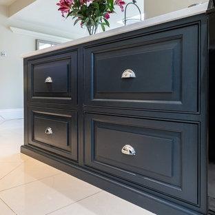 エセックスの大きいヴィクトリアン調のおしゃれなキッチン (ダブルシンク、レイズドパネル扉のキャビネット、青いキャビネット、珪岩カウンター、セラミックタイルの床、ベージュの床、白いキッチンカウンター) の写真
