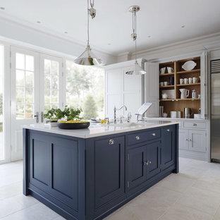 Inredning av ett klassiskt avskilt, stort kök, med skåp i shakerstil, rostfria vitvaror, en köksö, blå skåp och marmorgolv