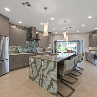 Photo of a contemporary kitchen in Miami with a single-bowl sink, flat-panel cabinets, grey cabinets, green splashback, stainless steel appliances, with island, beige floor and green benchtop.