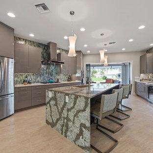 マイアミのコンテンポラリースタイルのおしゃれなアイランドキッチン (シングルシンク、フラットパネル扉のキャビネット、グレーのキャビネット、緑のキッチンパネル、シルバーの調理設備の、ベージュの床、緑のキッチンカウンター) の写真