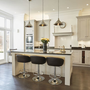 Inspiration for a large contemporary l-shaped eat-in kitchen in London with an integrated sink, shaker cabinets, grey cabinets, quartzite benchtops, black splashback, stainless steel appliances, with island and black benchtop.