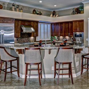 Imagen de cocina comedor en L, actual, de tamaño medio, con armarios estilo shaker, puertas de armario de madera oscura, salpicadero marrón, electrodomésticos de acero inoxidable, encimera de granito, salpicadero de azulejos de piedra, suelo de baldosas de porcelana y una isla