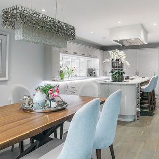 Inspiration for a mid-sized contemporary u-shaped open plan kitchen in Essex with an integrated sink, flat-panel cabinets, grey cabinets, window splashback, panelled appliances, vinyl floors, with island, brown floor and white benchtop.