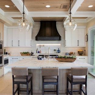 オレンジカウンティの広いトランジショナルスタイルのおしゃれなキッチン (落し込みパネル扉のキャビネット、白いキャビネット、クオーツストーンカウンター、白いキッチンパネル、セラミックタイルのキッチンパネル、パネルと同色の調理設備、ライムストーンの床、ベージュの床、白いキッチンカウンター) の写真
