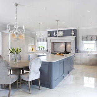 Large traditional u-shaped kitchen/diner in Other with a belfast sink, shaker cabinets, grey cabinets, quartz worktops, multi-coloured splashback, mosaic tiled splashback, stainless steel appliances, porcelain flooring and an island.