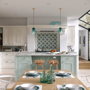 Inspiration for a large country l-shaped open plan kitchen in Manchester with shaker cabinets, marble benchtops, with island, blue cabinets and light hardwood floors.