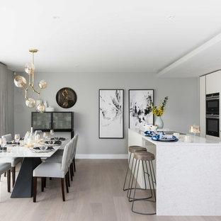 Immagine di una cucina abitabile contemporanea con lavello sottopiano, ante lisce, ante bianche, paraspruzzi marrone, elettrodomestici neri, parquet chiaro, isola e pavimento beige
