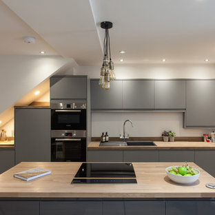 Inspiration for a small contemporary galley kitchen in London with a built-in sink, flat-panel cabinets, grey cabinets, wood worktops, white splashback, light hardwood flooring, an island and beige floors.