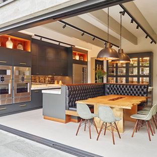 Design ideas for a contemporary u-shaped open plan kitchen in London with a submerged sink, shaker cabinets, grey cabinets, metallic splashback, stainless steel appliances, an island and multicoloured worktops.
