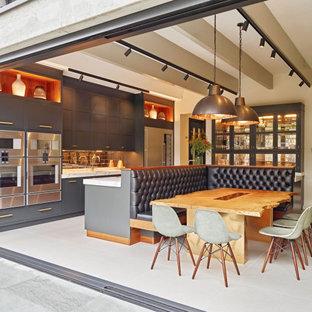Inredning av ett modernt flerfärgad flerfärgat kök, med en undermonterad diskho, skåp i shakerstil, grå skåp, stänkskydd med metallisk yta, rostfria vitvaror och en köksö