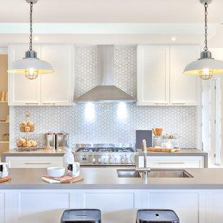 ワシントンD.C.の中サイズのモダンスタイルのおしゃれなキッチン (ドロップインシンク、白いキッチンパネル、セラミックタイルのキッチンパネル、シルバーの調理設備の、無垢フローリング、黄色い床) の写真