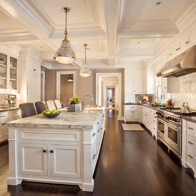 Enclosed kitchen - large traditional galley dark wood floor enclosed kitchen idea in New York with a farmhouse sink, white cabinets, marble countertops, white backsplash, stone tile backsplash, stainless steel appliances, an island and recessed-panel cabinets