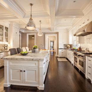 Geschlossene, Zweizeilige, Große Klassische Küche mit Landhausspüle, Schrankfronten im Shaker-Stil, weißen Schränken, Marmor-Arbeitsplatte, Küchenrückwand in Weiß, Rückwand aus Steinfliesen, Küchengeräten aus Edelstahl, dunklem Holzboden und Kücheninsel in New York