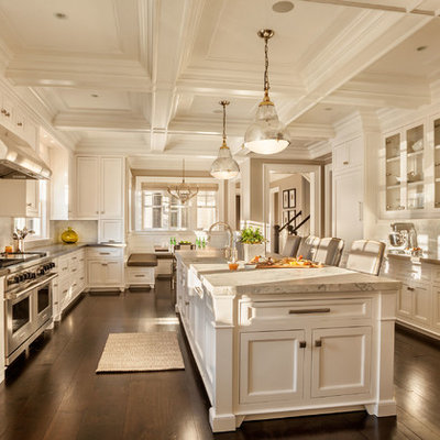 Large transitional u-shaped dark wood floor kitchen photo in New York with a farmhouse sink, shaker cabinets, white cabinets, marble countertops, white backsplash, porcelain backsplash, stainless steel appliances and an island