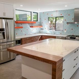 Exemple d'une petite cuisine américaine bord de mer en L avec un plan de travail en granite, une crédence bleue, un îlot central, un plan de travail blanc, un évier encastré, un placard à porte plane, des portes de placard en bois brun, une crédence en carreau de verre, un électroménager en acier inoxydable, un sol en carreaux de ciment et un sol gris.