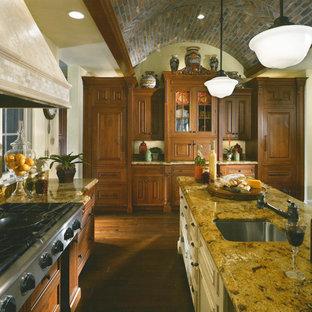 他の地域の広いサンタフェスタイルのおしゃれなキッチン (アンダーカウンターシンク、レイズドパネル扉のキャビネット、濃色木目調キャビネット、御影石カウンター、マルチカラーのキッチンパネル、テラコッタタイルのキッチンパネル、シルバーの調理設備、濃色無垢フローリング) の写真