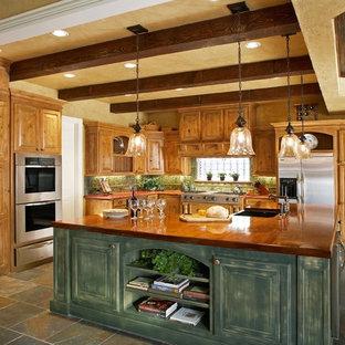 Ispirazione per una cucina rustica con elettrodomestici in acciaio inossidabile, top in legno e ante con finitura invecchiata