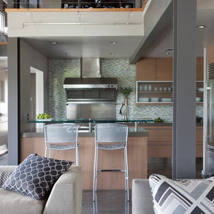 Industrial kitchen designs - Urban l-shaped gray floor and concrete floor kitchen photo in Chicago with flat-panel cabinets, light wood cabinets, green backsplash, stainless steel appliances, a peninsula and gray countertops