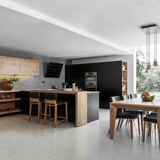 Inspiration for a mid-sized modern u-shaped eat-in kitchen in London with a single-bowl sink, flat-panel cabinets, dark wood cabinets, solid surface benchtops, stainless steel appliances, ceramic floors and with island.