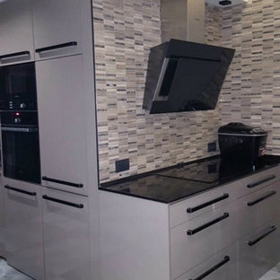 Expansive eclectic l-shaped open plan kitchen in Other with a triple-bowl sink, glass-front cabinets, grey cabinets, marble benchtops, multi-coloured splashback, ceramic splashback, black appliances, marble floors, with island and multi-coloured floor.