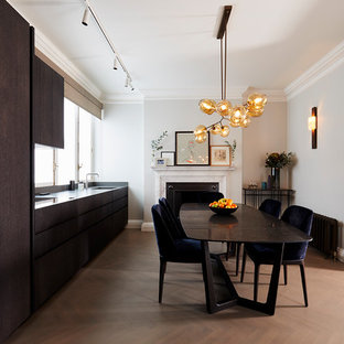 Design ideas for a medium sized contemporary single-wall kitchen/diner in London with an integrated sink, dark wood cabinets, granite worktops, black splashback, stainless steel appliances, no island, brown floors, black worktops, flat-panel cabinets and medium hardwood flooring.