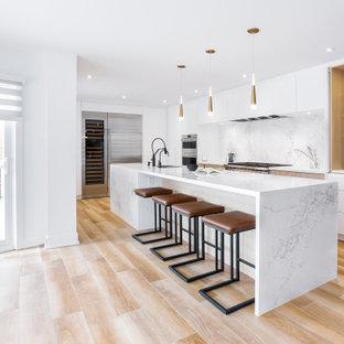 Esempio di una grande cucina design con lavello sottopiano, ante lisce, ante bianche, top in quarzo composito, paraspruzzi bianco, paraspruzzi in quarzo composito, elettrodomestici in acciaio inossidabile, pavimento in gres porcellanato, isola e top bianco