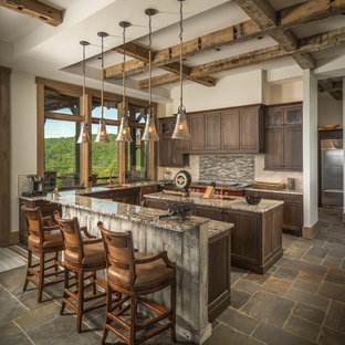 Country u-shaped kitchen in Charlotte with shaker cabinets, dark wood cabinets, grey splashback, multiple islands and brown floor.