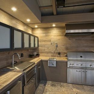サクラメントの大きいコンテンポラリースタイルのおしゃれなキッチン (ドロップインシンク、ガラス扉のキャビネット、濃色木目調キャビネット、タイルカウンター、茶色いキッチンパネル、セラミックタイルのキッチンパネル、シルバーの調理設備の、大理石の床、アイランドなし、グレーの床、茶色いキッチンカウンター) の写真