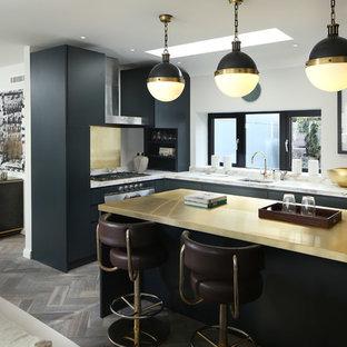Immagine di una cucina a L contemporanea con lavello sottopiano, ante lisce, ante nere, paraspruzzi a effetto metallico, paraspruzzi con piastrelle di metallo, pavimento in legno massello medio e isola