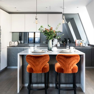 Contemporary l-shaped kitchen in London with flat-panel cabinets, white cabinets, stainless steel appliances, dark hardwood flooring, an island, brown floors and white worktops.